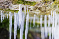 Frosty white icicles hanging from a rocky overhang micro-cave en Royalty Free Stock Photo