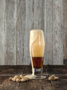 Frothy beer and peanuts. Royalty Free Stock Photo