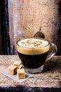 Frothy cup of espresso coffee with cane sugar topped with spri sprinkled chocolate on old grange dark background Royalty Free Stock Photo