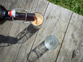 Frothy dark beer pouring into tall glasses from a brown glass bottle in summer garden on rustic wooden table process of selective Stock Image