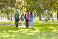 Froup of college students walking in the park full length a group young Stock Photos