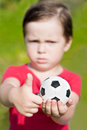 Frowning boy holding  soccer ball and shows thumb up. Focus on ball and hands Stock Photo