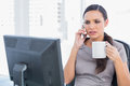 Frowning businesswoman holding coffee and answering phone in her office Stock Photos