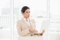 Frowning businesswoman standing behind her chair holding laptop in office Stock Photo
