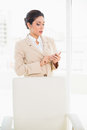 Frowning businesswoman standing behind her chair texting on her phone in office Royalty Free Stock Photo