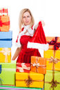 Frowning christmas woman holding santa hat surrounded by presents isolated on white background Stock Images