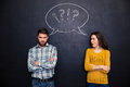 Frowning couple standing after argument over chalkboard background offended young with arms crossed Stock Photo