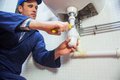Frowning plumber repairing sink in public bathroom Royalty Free Stock Photos
