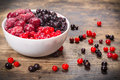 Frozen berries in plate on wooden background Royalty Free Stock Photo