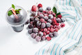 Frozen forest berries and cocktail in ice cubes on wooden table background. Royalty Free Stock Photo