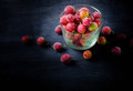 Frozen and fresh berries in a glass pial on a black background. Royalty Free Stock Photo