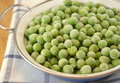 Frozen fresh peas in small casserole on wooden table Stock Photography
