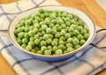 Frozen fresh peas in small casserole on wooden table Royalty Free Stock Photography