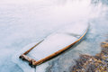 Frozen into ice of river lake pond old wooden boat forsaken r abandoned rowing fishing in winter Stock Image
