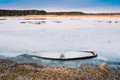 Frozen into ice of river lake pond old wooden boat forsaken r abandoned rowing fishing in winter at winter Royalty Free Stock Image