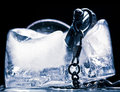 Frozen mechanical watch in ice macro Stock Photography