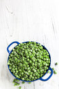 Frozen peas in blue colander baby small over white timber Stock Photo