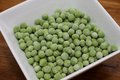 Frozen peas some green is thawing in a white bowl Royalty Free Stock Photography