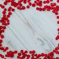 Frozen red currant on a white wooden background in the form of a frame on the edge Royalty Free Stock Photo