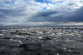 Frozen sea shore with stormy clouds and broken ice Royalty Free Stock Photo