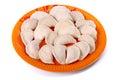 Frozen vareniki laying on the orange plate