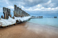 Frozen wooden breakwaters line to the world war II torpedo platform at Baltic Sea Royalty Free Stock Photo