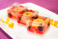 Fruit cake three square glass cups of with orange banana strawberry plums and grapes Stock Photos