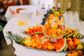 Fruit catering table with fresh juicy pineapples, grapes, water melon and peaches in glass vase Royalty Free Stock Photo
