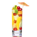 Fruit cocktail isolated on white. Fresh slices of mango, melon and grapes in the glass with mint and umbrellas on the top. Royalty Free Stock Photo