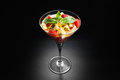 Fruit desert in the wineglass salad with pineapple orange passion strawberry and mint on dark background Stock Images