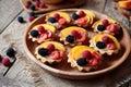Fruit dessert tartlets with vanilla custard and fresh raspberries, blackberry, peach. Dark rustic style. Royalty Free Stock Photo