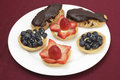 Fruit filled tarts and eclairs teatime treats of homemade with confectioner s custard topped with fresh strawberries or Royalty Free Stock Photography