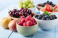 Fruit harvest selection in bowls a of different summer fruits a variety of on a painted blue wood planked farmhouse kitchen table Stock Photo