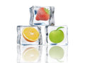 Fruit in ice cubes fresh frozen inside over a white background Royalty Free Stock Photography