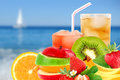 Fruit mix and cocktail on a beach background Royalty Free Stock Photo