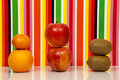 Fruit multicolored background apple orange mandarin kiwi two apples an a tangerine two kiwis are on a glossy surface with a behind Stock Photos