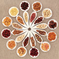 Fruit and nut selection large dried in white porcelain bowls over hessian background Stock Image