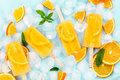 Fruit orange ice lolly and ice cubes and slices of orange on blu Royalty Free Stock Photo