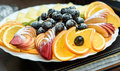 stock image of  fruit platter of beautifully sliced oranges, apples, peaches, kiwi and grapes close up
