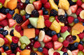 Fruit salad background featuring fresh berries and cut fruits as as blueberry blackberry green strawberries melon cantaloupe Royalty Free Stock Image