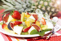 Fruit salad on the background of fresh pineapple healthy melon oranges figs strawberries and kiwi a white plate a Stock Image