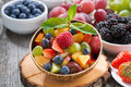 Fruit salad in a bamboo bowl and fresh berries close up horizontal Royalty Free Stock Images