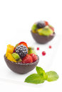 Fruit salad in chocolate cups on white background with fresh mint Royalty Free Stock Images
