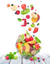 Fruit salad in glass bowl with ingredients in the air on white wooden table Royalty Free Stock Photo