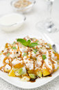 Fruit salad with nuts yogurt and mint vertical closeup on a white plate Stock Photos