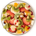 Fruit salad in the salad bowl a transparent ingredients green kiwi yellow banana plum red orange orange red garnet small pieces Stock Image