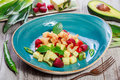 Fruit salad with shrimp, avocado, bulgarian pepper, kiwi, pineapple, raspberries in plate on wooden background close up.