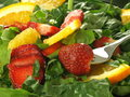 Fruit salad with spinach closeup of strawberry orange and Stock Photography