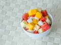 Fruit salad in the white bowl on the creamy tablecloth Stock Photography