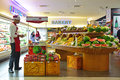 A fruit section island and a promotional booth with a promoter in a supermarket in Asia